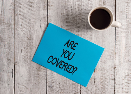 Text sign showing Are You Covered Question. Business photo showcasing asking showing if they had insurance in work or life Pastel Colour paper placed next to a cup of coffee above the wooden table 写真素材