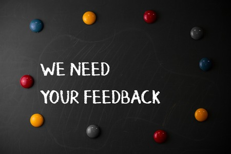 Text sign showing We Need Your Feedback. Business photo showcasing criticism given to say can be done improvement Round Flat shape stones with same sizes stick to old chalk black board