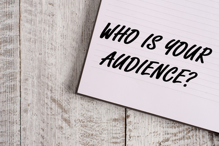 Conceptual hand writing showing Who Is Your Audience Question. Concept meaning who is watching or listening to it Notebook stationary placed above classic wooden backdrop Stok Fotoğraf