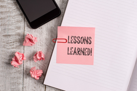 Conceptual hand writing showing Lessons Learned. Concept meaning experiences distilled project that should actively taken Notebook stationary placed above classic wooden backdrop