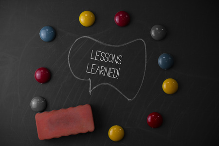 Handwriting text writing Lessons Learned. Conceptual photo experiences distilled project that should actively taken Round Flat shape stones with one eraser stick to old chalk black board Stock Photo