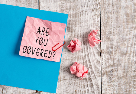 Writing note showing Are You Covered Question. Business concept for asking showing if they had insurance in work or life Wrinkle paper and cardboard placed above wooden background