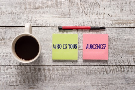 Text sign showing Who Is Your Audience Question. Business photo text who is watching or listening to it Stationary placed next to a cup of black coffee above the wooden table