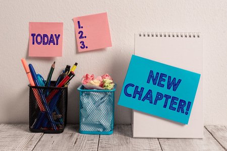 Writing note showing New Chapter. Business concept for Starting ultimately something goals created in your mind Sticky Notes Card on Wall Spiral Notebook 2 Mesh Pencil Pots Work Desk