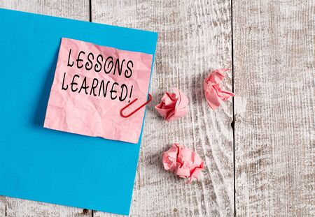 Writing note showing Lessons Learned. Business concept for experiences distilled project that should actively taken Wrinkle paper and cardboard placed above wooden background