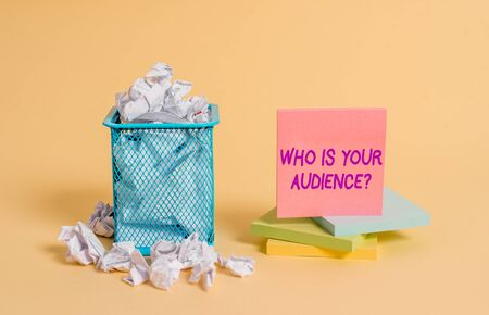 Conceptual hand writing showing Who Is Your Audience Question. Concept meaning who is watching or listening to it crumpled paper and stationary paper placed in the trash can Stok Fotoğraf