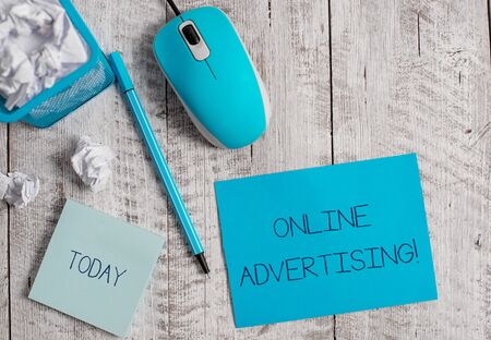 Conceptual hand writing showing Online Advertising. Concept meaning Internet Web Marketing to Promote Products and Services Crumpled paper in bin and computer mouse on wooden backdrop.