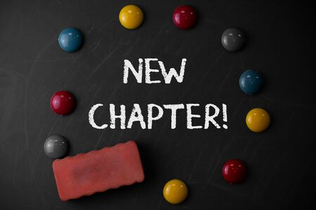 Word writing text New Chapter. Business photo showcasing Starting ultimately something goals created in your mind Round Flat shape stones with one eraser stick to old chalk black board Stok Fotoğraf