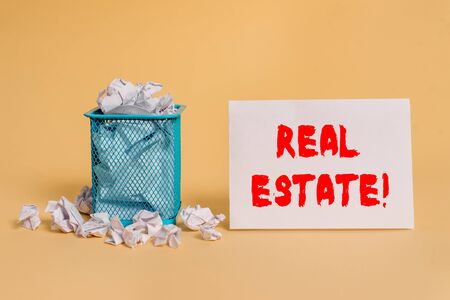 Handwriting text Real Estate. Conceptual photo owning property consisting of empty land or buildings crumpled paper trash and stationary with empty paper placed in trash can Stock Photo