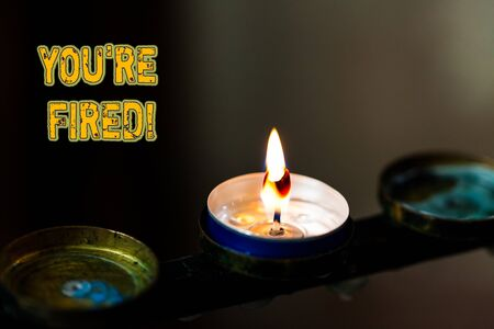 Text sign showing You Re Fired. Business photo showcasing Used by boss indicate employee that he is discharged from job Abstract burning candle set of three just one shining flame glowing dark