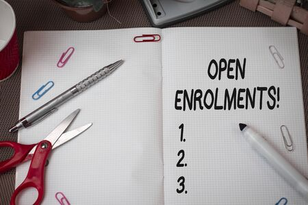 Text sign showing Open Enrolments. Business photo showcasing when employees may make changes to elected fringe benefit Scissors and writing equipments plus math book above textured backdrop