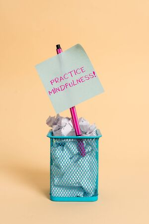 Conceptual hand writing showing Practice Mindfulness. Concept meaning achieve a State of Relaxation a form of Meditation crumpled paper and stationary with paper placed in the trash can