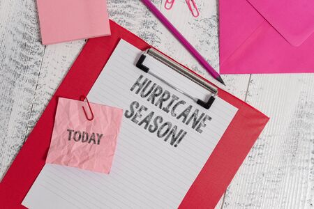 Handwriting text writing Hurricane Season. Conceptual photo time when most tropical cyclones are expected to develop Clipboard sheet pencil crushed note envelope clips notepad wood background