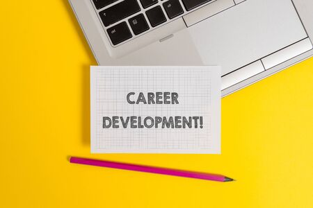 Handwriting text writing Career Development. Conceptual photo Lifelong learning Improving skills to get a better job Top trendy metallic laptop pencil squared paper sheet colored background