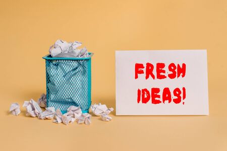 Handwriting text Fresh Ideas. Conceptual photo thought or suggestion as to a possible course of action crumpled paper trash and stationary with empty paper placed in trash can Stock Photo