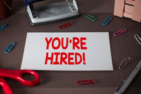 Text sign showing You Re Hired. Business photo text Used by huanalysis resources indicate employee that he is got job Scissors and writing equipments plus plain sheet above textured backdrop