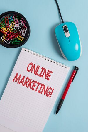 Text sign showing Online Marketing. Business photo text leveraging web based channels spread about companys brand Notebook and writing equipment with computer mouse above pastel backdrop 写真素材