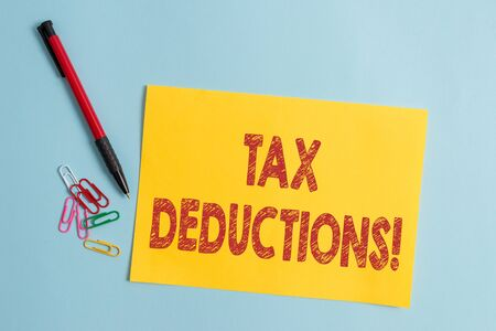 Handwriting text Tax Deductions. Conceptual photo reduction income that is able to be taxed of expenses Plain cardboard and writing equipment placed above pastel colour backdrop
