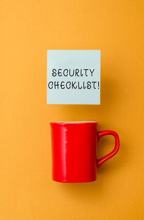 Conceptual hand writing showing Security Checklist. Concept meaning Protection of Data and System Guide on Internet Theft Front view coffee cup colored sticky note yolk color background