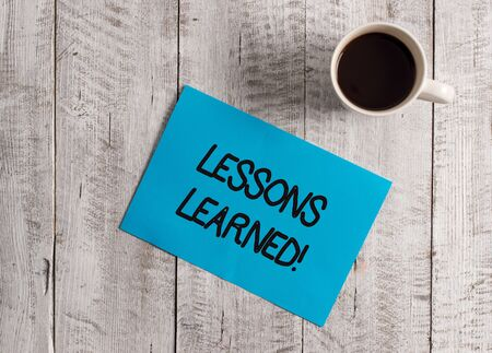 Text sign showing Lessons Learned. Business photo showcasing experiences distilled project that should actively taken Pastel Colour paper placed next to a cup of coffee above the wooden table Stock Photo