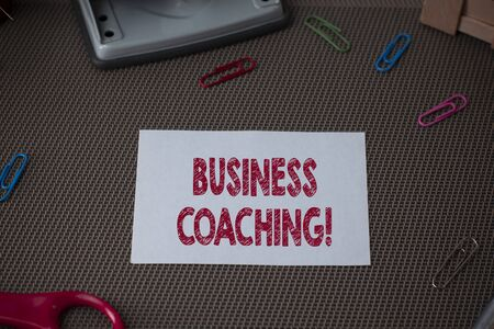 Conceptual hand writing showing Business Coaching. Concept meaning Helping employees become more active Consulting an expert Scissor and writing equipments sheet above textured backdrop