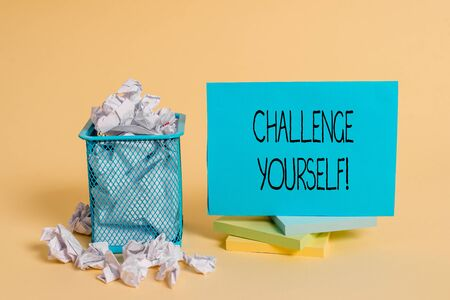 Writing note showing Challenge Yourself. Business concept for Setting Higher Standards Aim for the Impossible crumpled paper and stationary with paper placed in the trash can Stockfoto