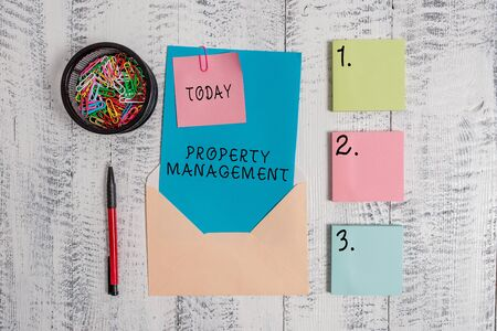 Writing note showing Property Management. Business concept for Overseeing of Real Estate Preserved value of Facility Envelope letter sticky note ballpoint clips on wooden background Stock Photo