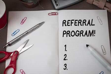 Text sign showing Referral Program. Business photo showcasing internal recruitment method employed by organizations Scissors and writing equipments plus math book above textured backdrop