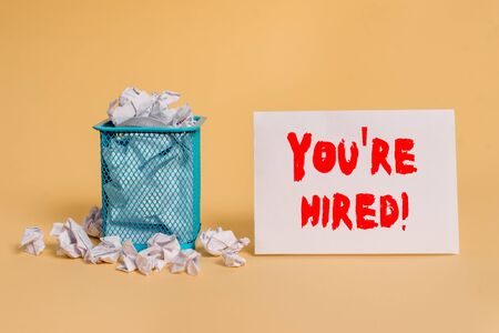 Handwriting text You Re Hired. Conceptual photo Used by huanalysis resources indicate employee that he is got job crumpled paper trash and stationary with empty paper placed in trash can
