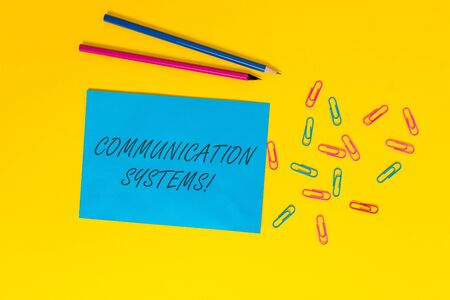 Writing note showing Communication Systems. Business concept for Flow of Information use of Machine to transmit signals Blank paper sheet message reminder pencils clips colored background
