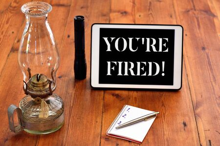 Word writing text You Re Fired. Business photo showcasing Used by boss indicate employee that he is discharged from job Writing equipments placed next to gadget plus a classic vintage lantern Stock Photo