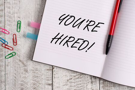 Conceptual hand writing showing You Re Hired. Concept meaning Used by huanalysis resources indicate employee that he is got job Notebook stationary placed above classic wooden backdrop