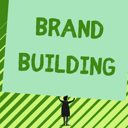 Word writing text Brand Building. Business photo showcasing Generating awareness Establishing and promoting company Man stands in back view under huge empty blank big tilted rectangle board