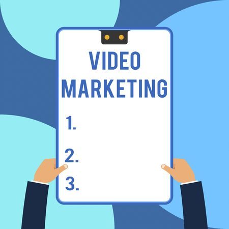 Conceptual hand writing showing Video Marketing. Concept meaning create short videos about specific topics using articles Male hands holding electronic device geometrical background Banco de Imagens