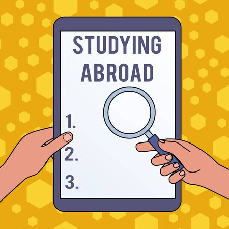Handwriting text writing Studying Abroad. Conceptual photo learn outside of home in foreign country Travelling Hands Holding Magnifying Glass Against Switched Off Touch Screen Tablet