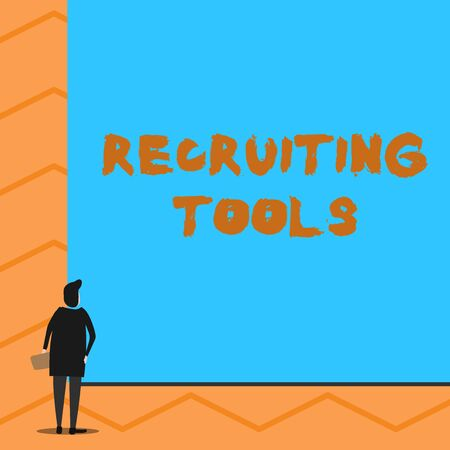 Text sign showing Recruiting Tools. Business photo text getting new talents to your company through internet or ads Man stands in back view in front of huge empty blank big rectangle board Banco de Imagens - 124992147