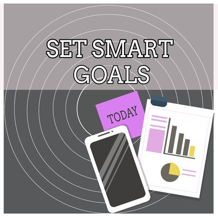 Text sign showing Set Smart Goals. Business photo text giving criteria to guide in the setting of objectives Layout Smartphone Off Sticky Notes Clipboard with Pie Chart and Bar Graph 版權商用圖片