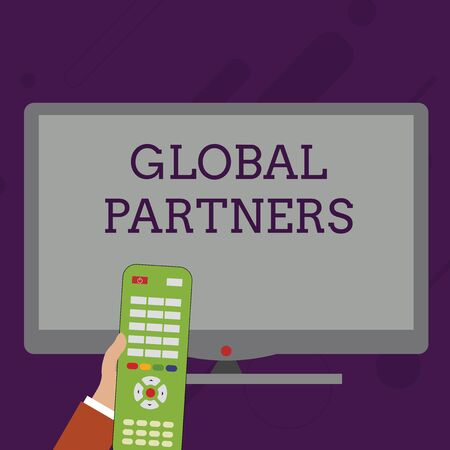 Word writing text Global Partners. Business photo showcasing Two or more firms from different countries work as a team Hand Holding Computer Remote Control infront of Blank Wide Color PC Screen Reklamní fotografie