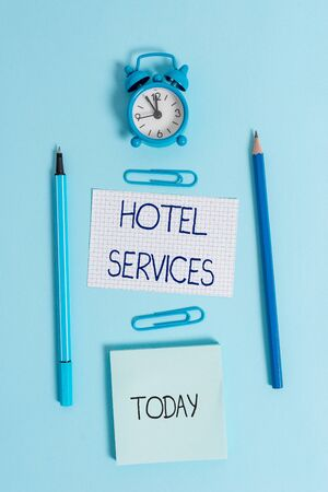 Writing note showing Hotel Services. Business concept for Facilities Amenities of an accommodation and lodging house Alarm clock squared paper sheet notepad markers colored background Фото со стока