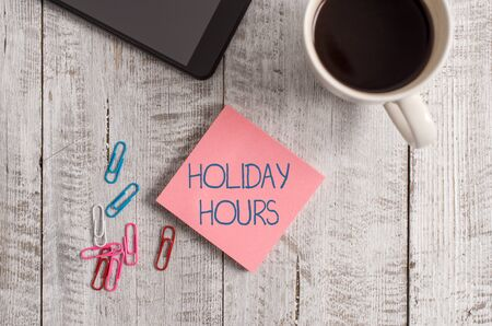 Handwriting text writing Holiday Hours. Conceptual photo employee receives twice their normal pay for all hours Stationary placed next to a cup of black coffee above the wooden table