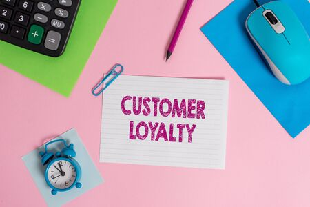 Word writing text Customer Loyalty. Business photo showcasing result of consistently positive emotional experience Mouse calculator sheets clip marker note alarm clock colored background Фото со стока