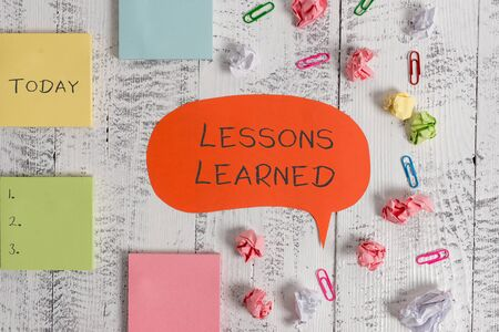 Word writing text Lessons Learned. Business photo showcasing the knowledge or understanding gained by experience Blank speech bubble paper balls clips sticky notes old wooden background Zdjęcie Seryjne - 125249214