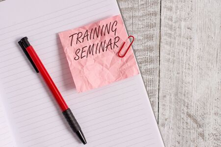 Text sign showing Training Seminar. Business photo text Academic instruction Formal presentation of a research Wrinkle paper and notebook plus stationary placed above wooden background Zdjęcie Seryjne