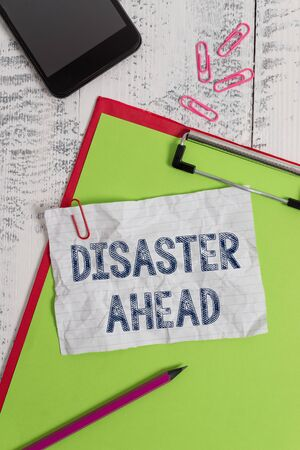 Handwriting text Disaster Ahead. Conceptual photo Contingency Planning Forecasting a disaster or incident Clipboard paper sheet pencil smartphone note clips wooden retro background