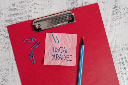 Writing note showing Fiscal Paradise. Business concept for The waste of public money is a great concern topic Colored clipboard crushed sticky note clip marker old wooden background