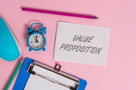 Writing note showing Value Proposition. Business concept for feature intended to make a company or product attractive Alarm clock clipboard paper sheets mouse markers colored background