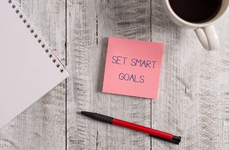 Handwriting text Set Smart Goals. Conceptual photo giving criteria to guide in the setting of objectives Stationary placed next to a cup of black coffee above the wooden table Archivio Fotografico