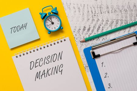 Conceptual hand writing showing Decision Making. Concept meaning The act of deciding between two or more possibilities Spiral notepad sheet marker alarm clock wooden background