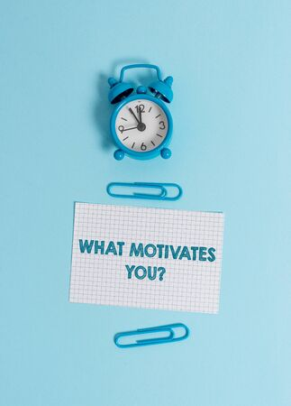 Handwriting text writing What Motivates Youquestion. Conceptual photo know reasons why you want to wake up each morning Alarm clock wakeup squared blank paper sheet clips colored background