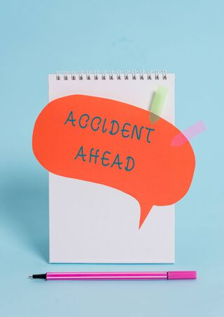Conceptual hand writing showing Accident Ahead. Concept meaning Unfortunate event Be Prepared Detour Avoid tailgating Spiral notepad speech bubble arrow pen lying pastel background